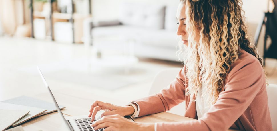 Young successful woman working from home at laptop.